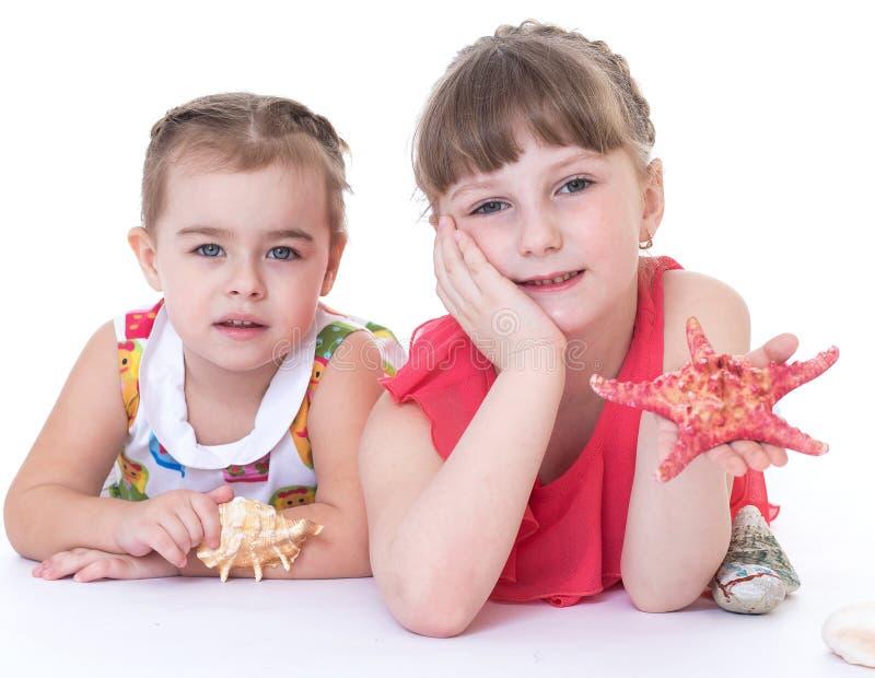 Twee meisjes spelen en shells stock foto's