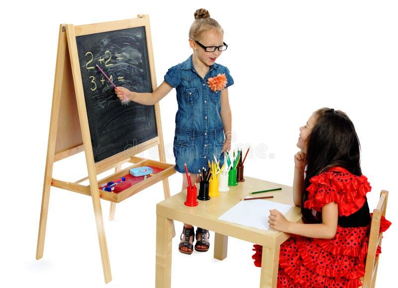 Twee meisjes spelen in school (reeks) stock afbeelding