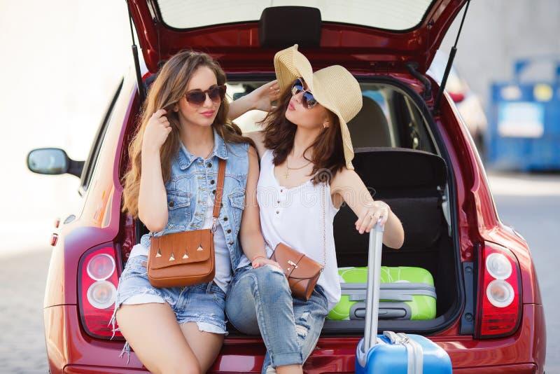 Twee meisjes spreken, die in open autoboomstam zitten stock afbeelding