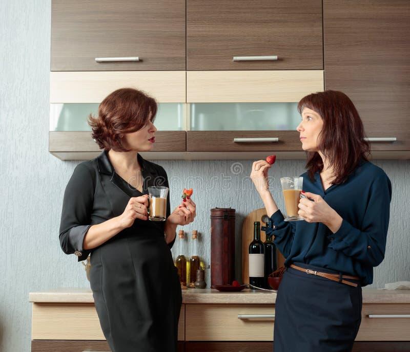 Twee meisjes spreken en drinken koffie in de keuken royalty-vrije stock afbeeldingen