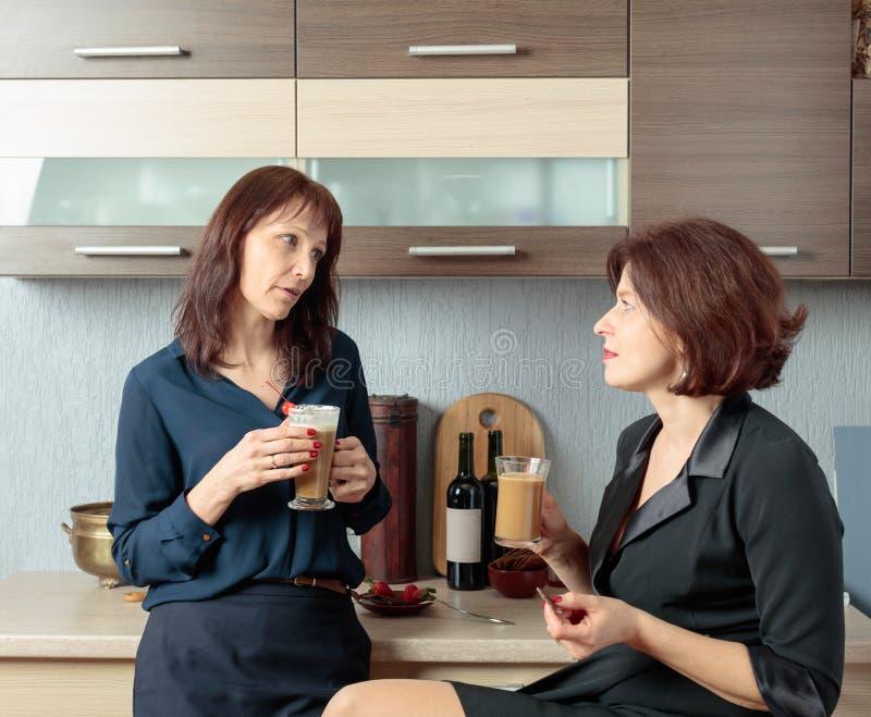 Twee meisjes spreken en drinken koffie in de keuken stock foto's