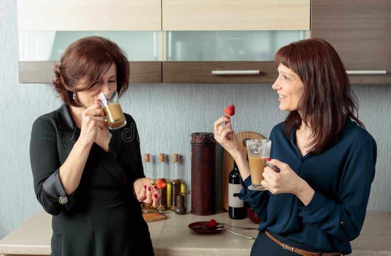 Twee meisjes spreken en drinken koffie in de keuken stock afbeelding