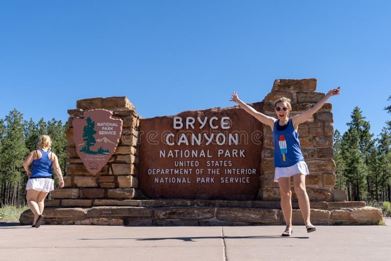 Twee meisjes stellen in dwaze posities bij het Bryce Canyon National Park-teken stock foto