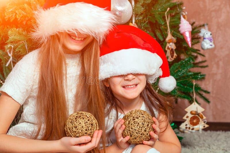 Twee meisjes stellen en voor de gek houden rond de Kerstboom stock foto's