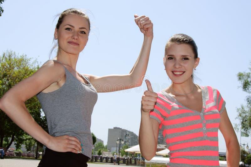 Twee meisjes tonen wat zij sterk zijn stock afbeelding