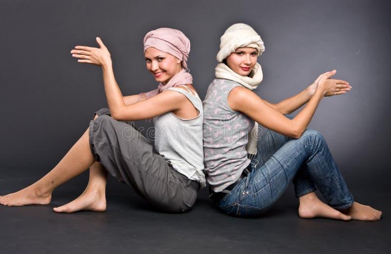 Twee meisjes in tulbanden zit op vloer stock afbeelding