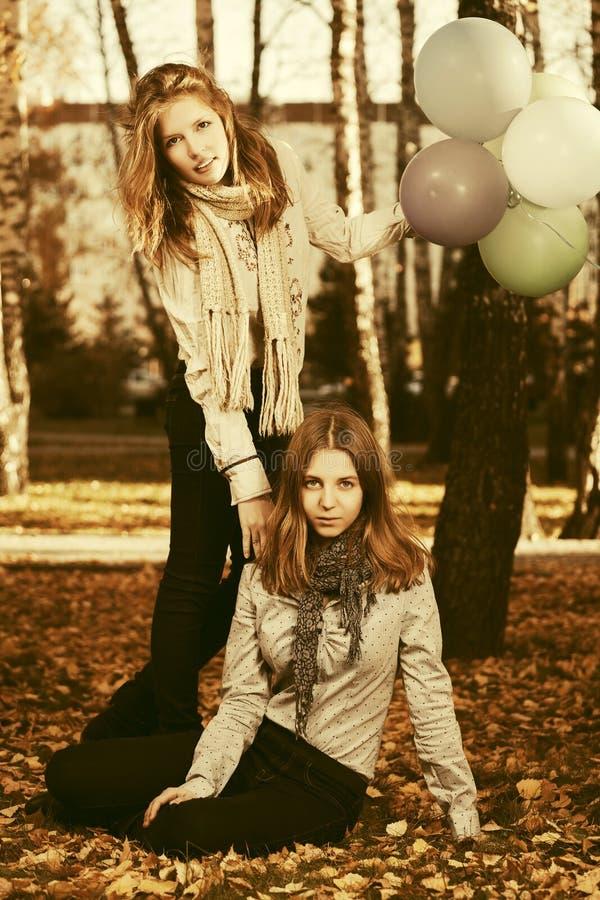 Twee meisjes van de maniertiener met ballons in de herfstpark royalty-vrije stock afbeeldingen