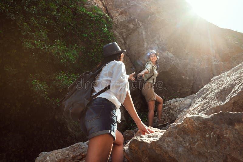 Twee meisjes van een toeristen` s meisje beklimmen de bergen, helpen elkaar, bereiken uit een helpende hand stock foto