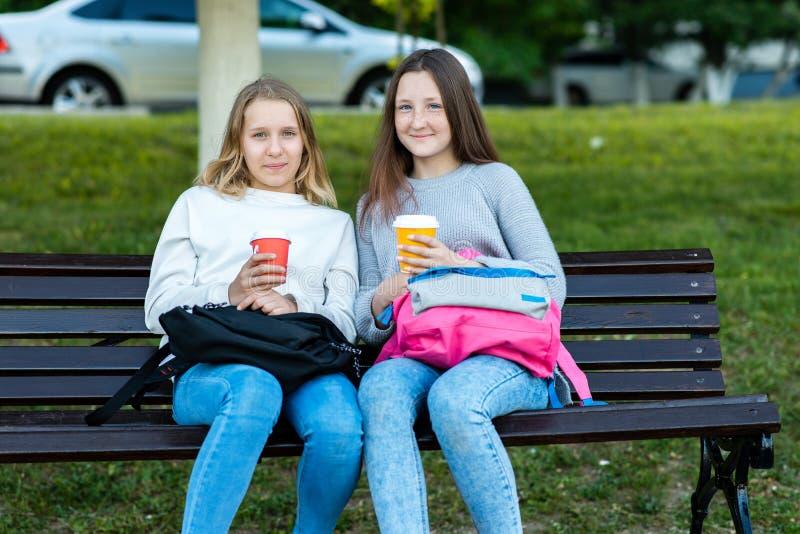 Twee meisjes van het meisjesschoolmeisje De zomer in het park zit op een bank In zijn handen houdt hij rugzakken, glazen met heet stock fotografie