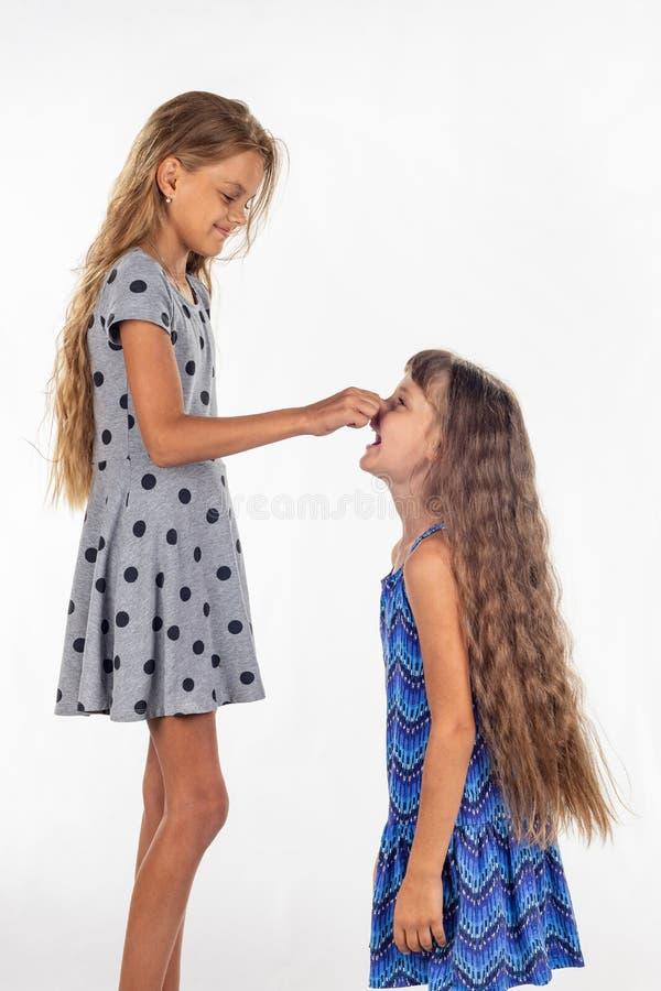 Twee meisjes van verschillende gestalte, één bevonden zich op een stoel en trekt het andere meisje door de neus royalty-vrije stock foto