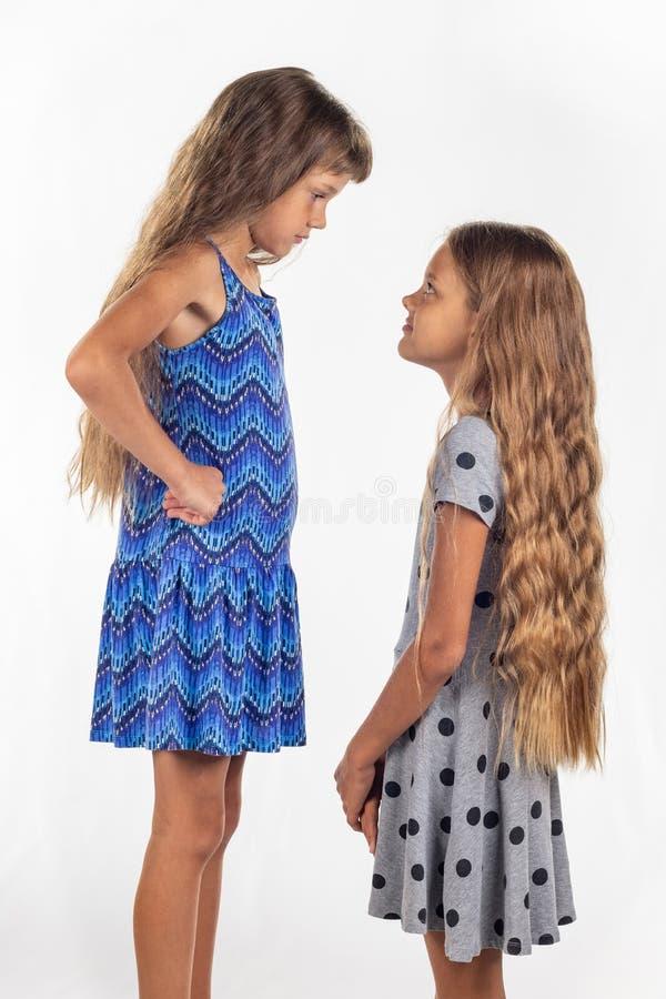 Twee meisjes van verschillende gestalte, één van hen bevonden zich op een stoel langer te zijn dan andere stock foto