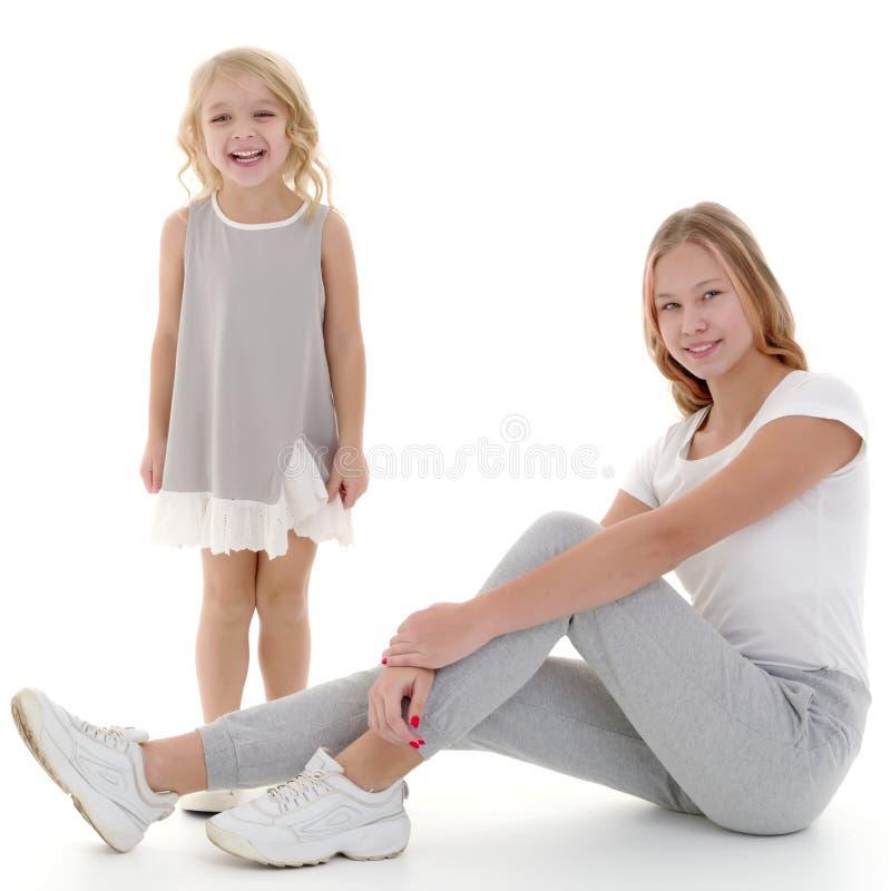 Twee meisjes van verschillende leeftijden in de studio op een witte achtergrond royalty-vrije stock afbeelding