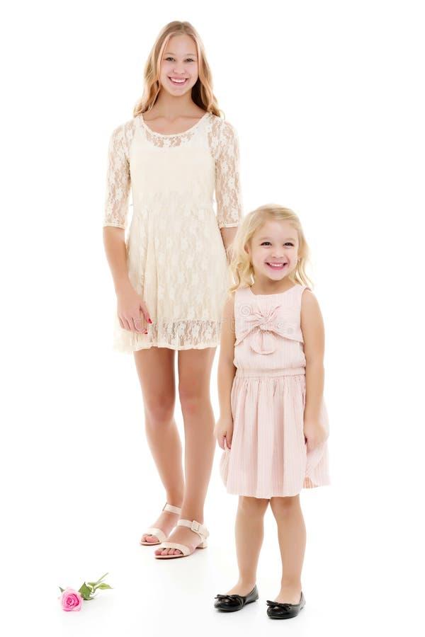 Twee meisjes van verschillende leeftijden in de studio op een witte achtergrond royalty-vrije stock fotografie