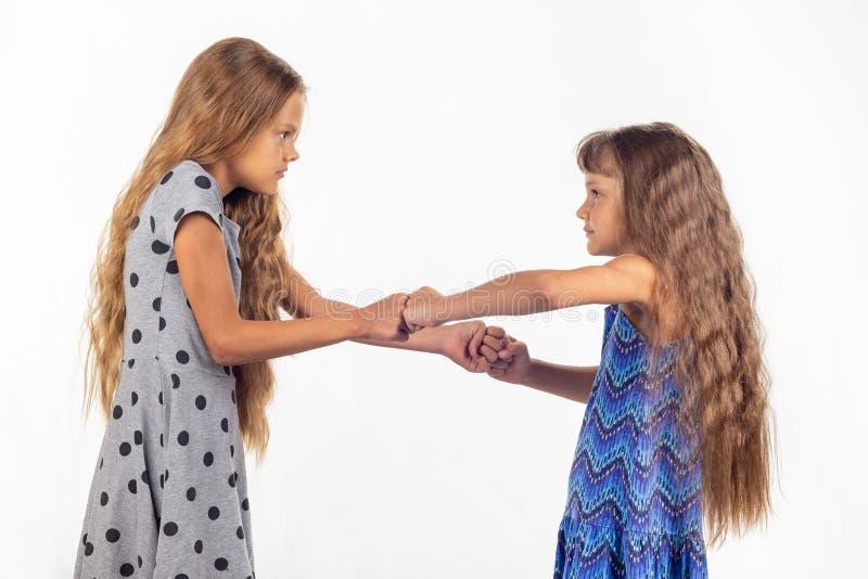 Twee meisjes vechten, grijpend elkaars vuisten stock foto's