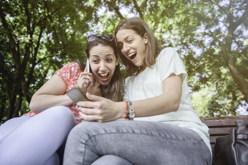 Twee meisjes verrassen sociale media onverwachte de media van de de jeugd millennial vriendschap conceptenverslaving aan de leven stock fotografie
