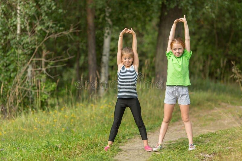 Twee meisjes voeren in openlucht gymnastiek- oefeningen uit Sport stock foto
