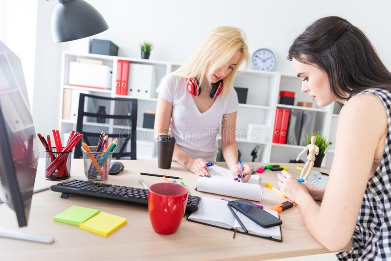 Twee meisjes werken in het bureau Het meisje houdt een model van een mens royalty-vrije stock afbeeldingen