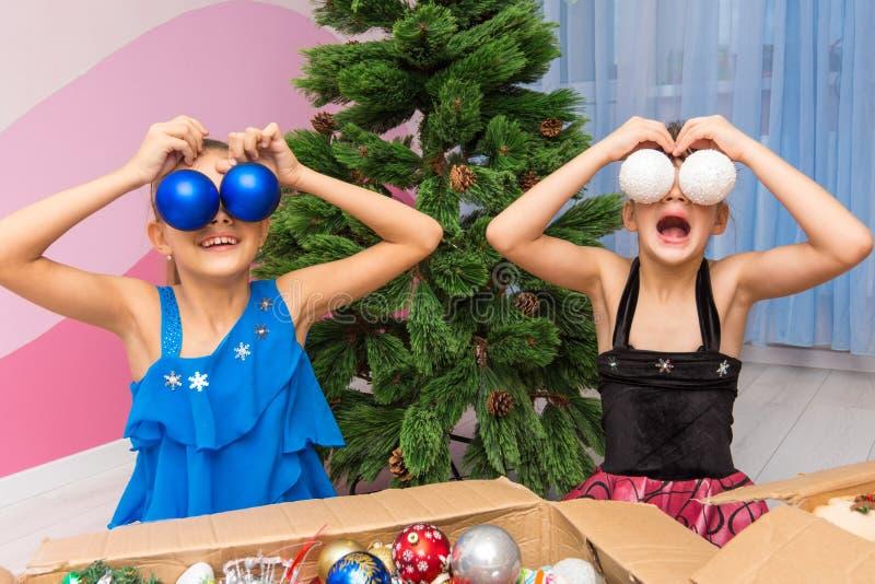 Twee meisjes zetten grote Kerstmisballen aan hun ogen royalty-vrije stock fotografie
