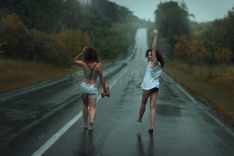 Twee meisjes zijn op rijweg in de regen stock foto's