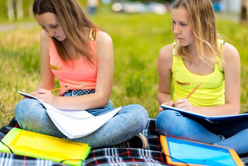Twee meisjes zijn vrouwelijke studenten In de zomer doen zij hun thuiswerk in aard Het concept schoolklassen in aard stock fotografie