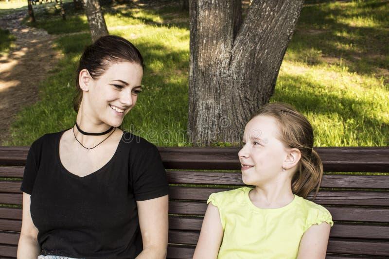 Twee meisjes zitten op een en bank die spreken lachen stock foto