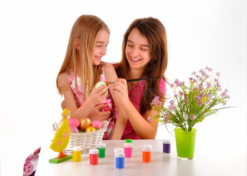 Twee meisjes - zusters die pret hebben die Paaseieren schilderen royalty-vrije stock afbeelding