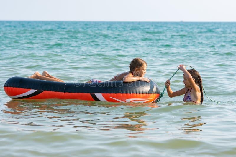 Twee meisjes zwemmen in het overzees met een opblaasbare boot stock afbeeldingen