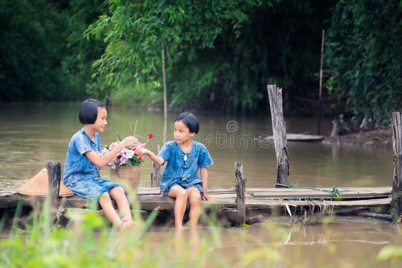 Twee meisjeskinderen die en water samen op houten brug over moeras, Aziatische jonge geitjes zitten spelen die water spelen stock afbeelding