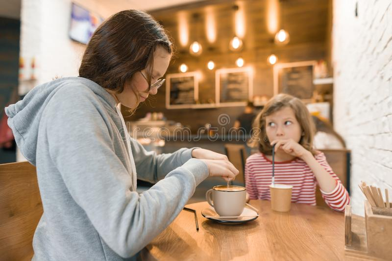 Twee meisjeskinderen in koffie, drinken melkdranken stock foto