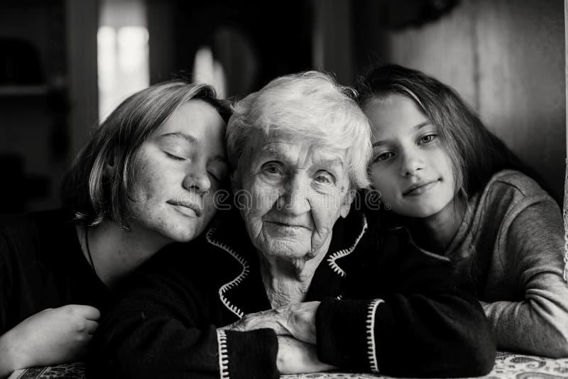 Twee meisjeskleindochter die haar grootmoeder kust Familie stock afbeelding