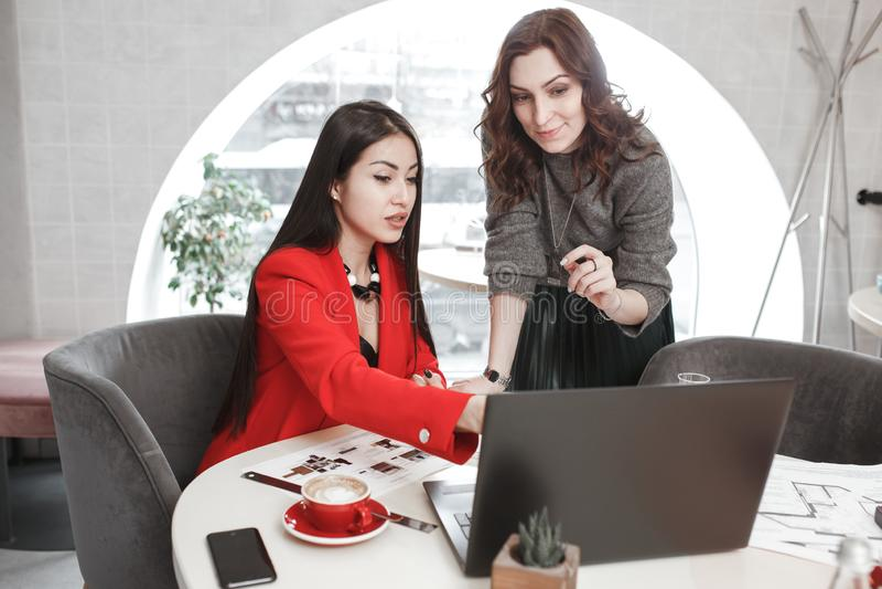 Twee meisjesontwerpers werken met laptop en documentatie bij het project in het modieuze bureau Projectverwezenlijking stock fotografie