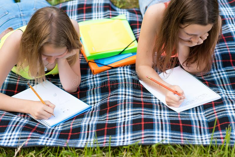 Twee meisjesschoolmeisje In de zomer op een plaid Hij rust na het instituut Schrijf nota's in een notitieboekjeconcept lessen royalty-vrije stock foto