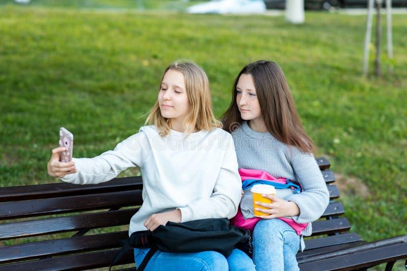 Twee meisjesschoolmeisje In de zomer in park op de straattieners Houdt een glas koffie of thee Gefotografeerd op stock afbeeldingen