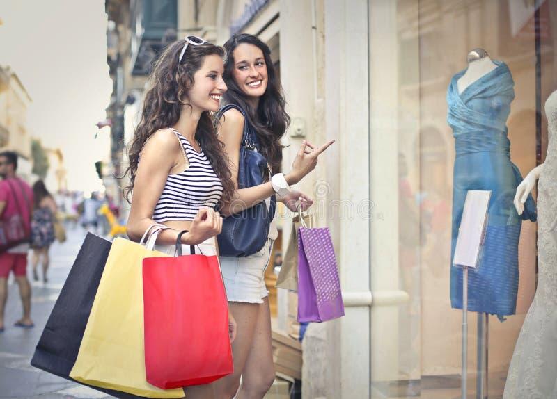 Twee meisjesvenster het winkelen royalty-vrije stock afbeeldingen