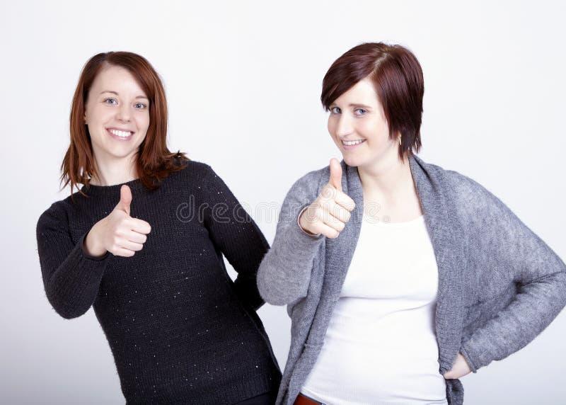 Twee meisjesvrienden die duim omhoog gesturing stock afbeelding