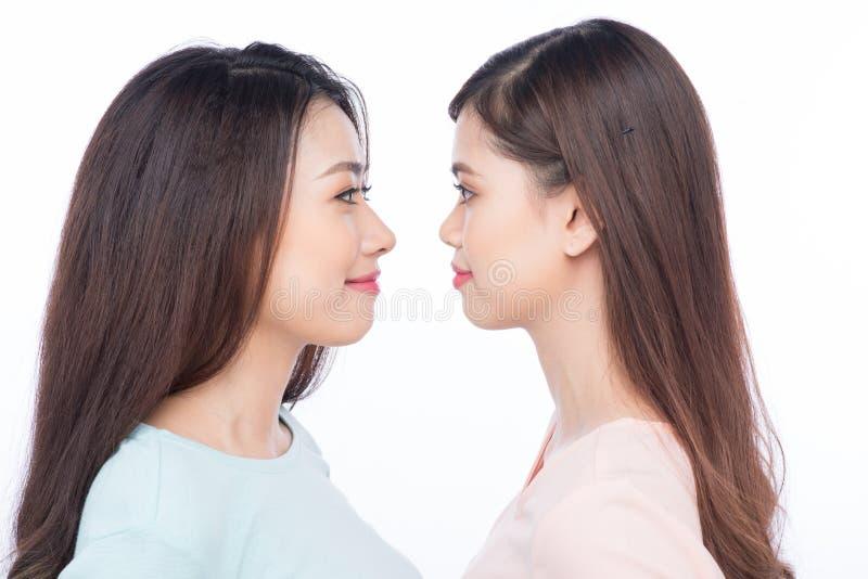 Twee meisjesvrienden die elkaar bekijken het glimlachen stock afbeeldingen