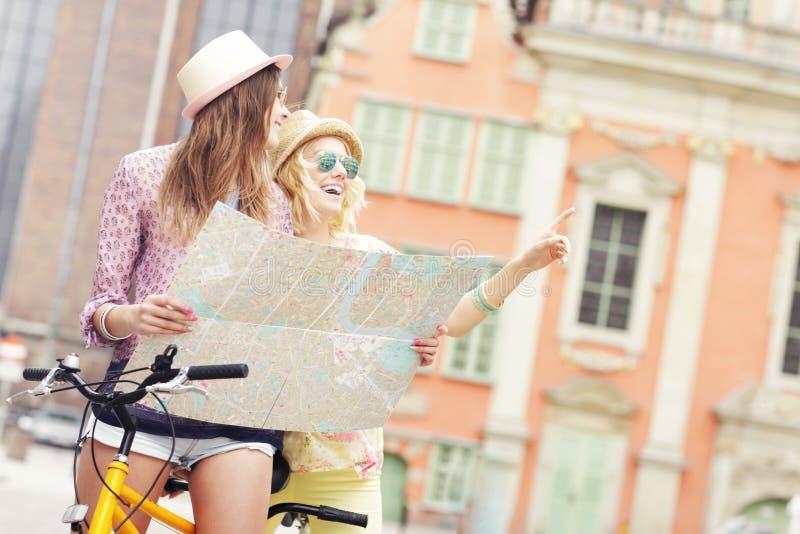 Twee meisjesvrienden die kaart gebruiken terwijl het berijden van fiets achter elkaar stock foto's