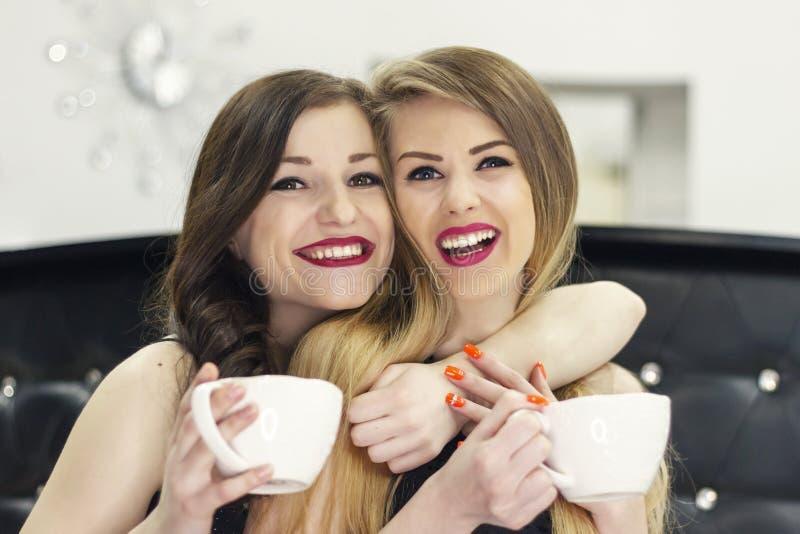 Twee meisjesvrienden die thee koffie en het lachen drinken royalty-vrije stock foto