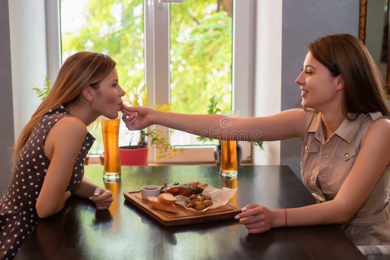 Twee meisjesvrienden hebben lunch in restaurant Men voedt andere stock afbeeldingen