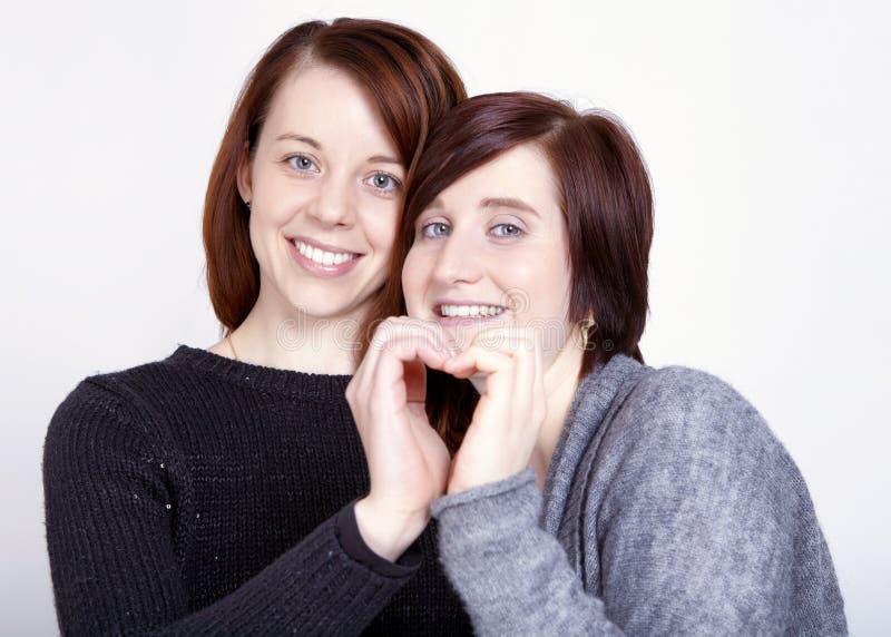 Twee meisjesvrienden maken een hart met handen stock foto