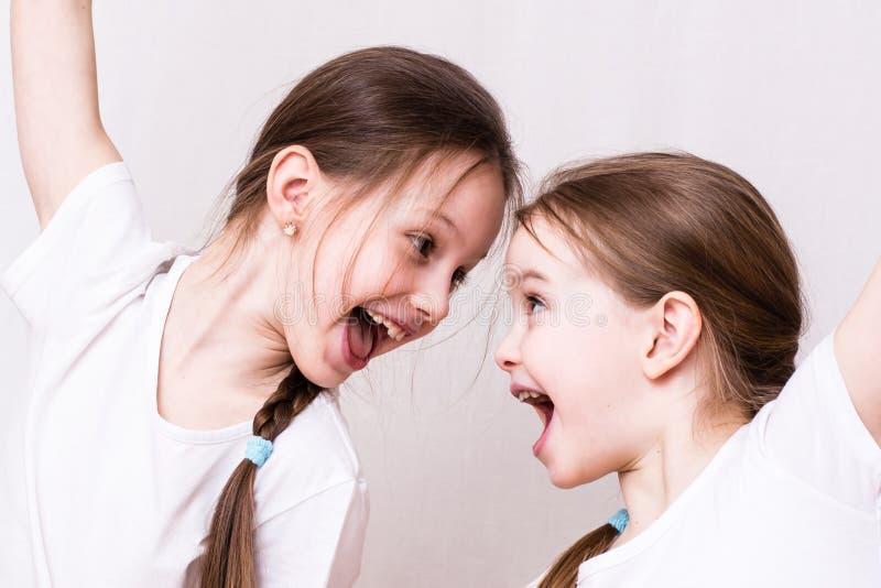 Twee meisjeszusters glimlachen emotioneel bij elkaar royalty-vrije stock foto's