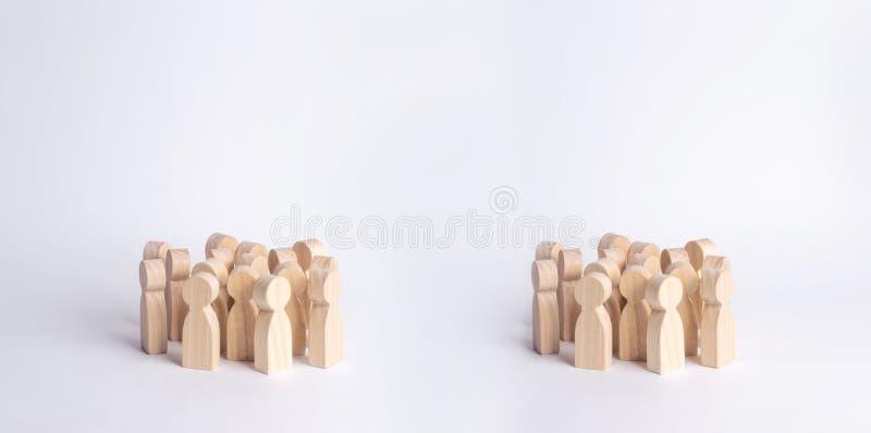Twee menigten van houten cijfers van mensen bevinden zich op een witte achtergrond Het concept verschillende sociale groepen, de  royalty-vrije stock foto's