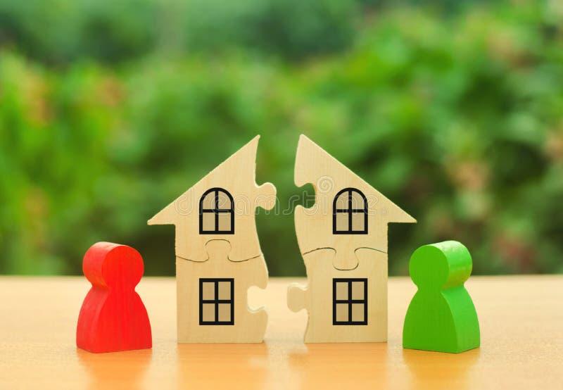Twee menselijke cijfers verdelen het huis onder zich Scheidingsconcept Geschillen over afdelingsproces van onroerende goederen en stock foto's
