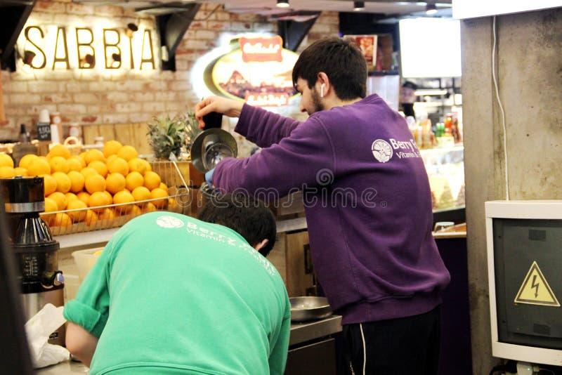 Twee mensen bereiden vers gedrukt natuurlijk sap, voedselhof in de centrale markt voor royalty-vrije stock afbeelding