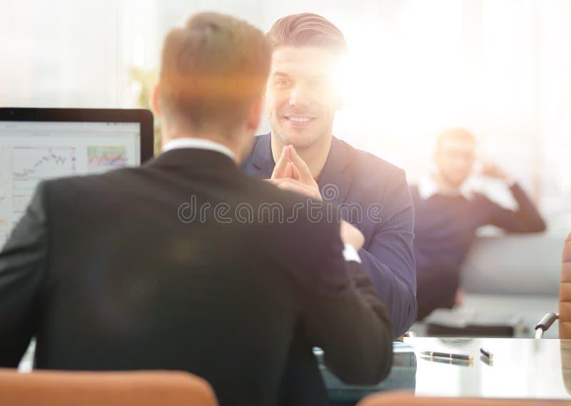 Twee mensen bespreken de groei van het bedrijf, die de het toenemen grafiek op het computerscherm bekijken stock foto