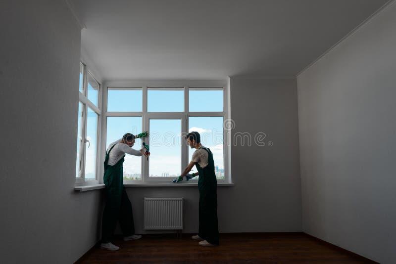 Twee mensen bevestigen venster stock afbeeldingen
