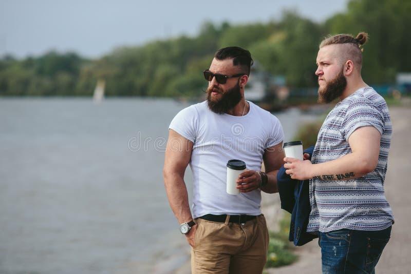 Twee mensen bevinden zich en drinken koffie royalty-vrije stock fotografie