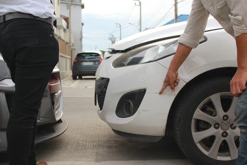 Twee mensen debatteerden na autoneerstorting op stadsstraat, Ongevallenconcept stock foto