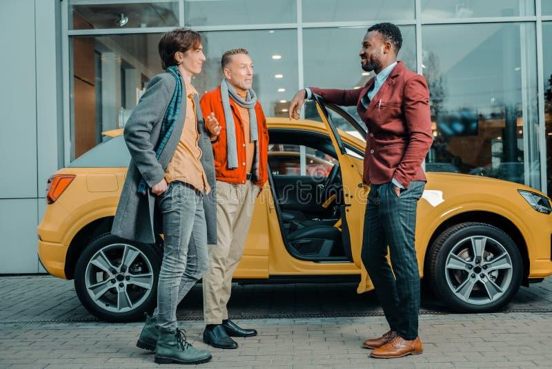 Twee mensen die aan een autohandelaar spreken na het kopen van auto stock foto
