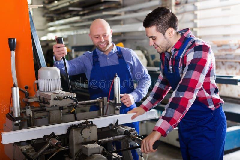 Twee mensen die aan machine werken stock afbeeldingen